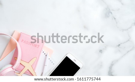 Summer vacation and travel concept. Flat lay design with airplane, pink passport, paper notepad, headphones, smartphone on marble background. Top view with copy space.