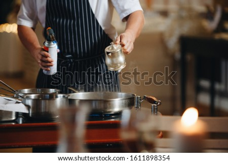 The chef prepares food in front of the visitors in the restaurant close up.