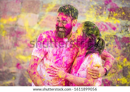 Happy fun loving asian indian couple painted in colors celebrating holi festival outdoor, love and relationship #1611899056