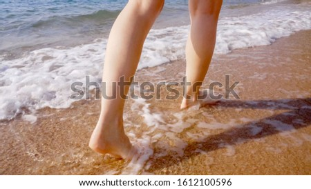 A woman walks along the golden sand of a beach. Female legs walk by the sea. Bare feet of a woman walking along a sandy shore with waves. Summer vacation or vacation. #1612100596