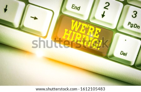 Text sign showing We Re Hiring. Conceptual photo recently employ someone or pay him to do particular job White pc keyboard with empty note paper above white background key copy space. #1612105483