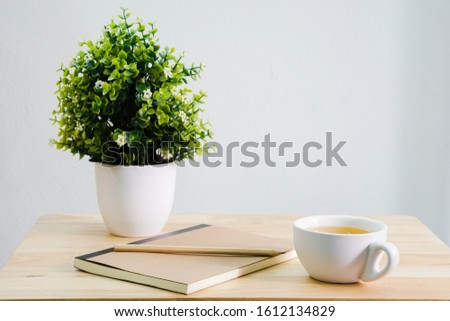 Side view of a desk with green artificial plants in white plant pots and jasmine tea in white tea glasses.  A pencil placed on a brown notebook, copy space #1612134829