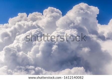 Cumulus cloudscape seen from a window plane #1612140082
