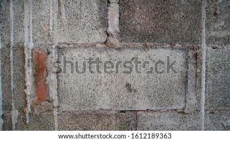 Gray cement background with orange bricks #1612189363