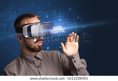 Businessman looking through Virtual Reality glasses with WEB TRAFFIC inscription, social networking concept #1612208401