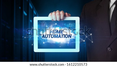 Young business person working on tablet and shows the inscription: HOME AUTOMATION #1612210573