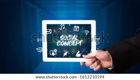 Young business person working on tablet and shows the inscription: SOCIAL CONCEPT #1612210594
