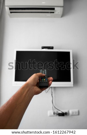 The man with the remote control in hand want switch on the TV and presses the button on the remote control. Remote control in hand closeup. #1612267942