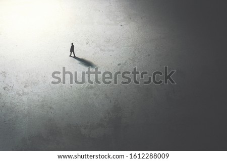 man walking in the night toward the light Royalty-Free Stock Photo #1612288009