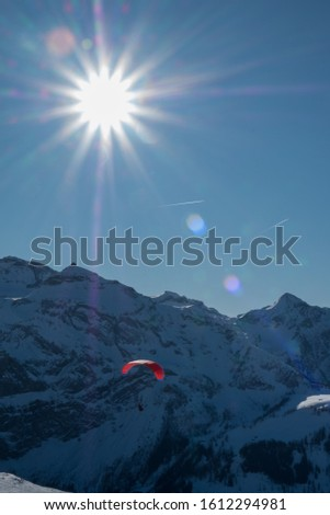 Paragliding Over Mountain In Winter, picture taken against the sun, with sun flare
