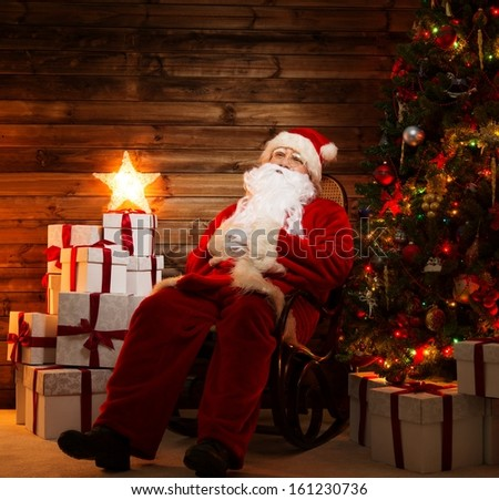 Santa Claus sitting on rocking chair in wooden home interior with illuminated star on gift boxes  #161230736