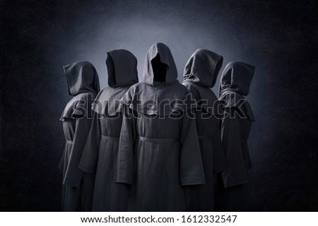 Group of five scary figures in hooded cloaks in the dark #1612332547