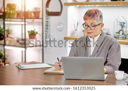 Modern senior business lady writing company profit in her notebook. Mature woman in blazer and glasses, white light office #1612353025