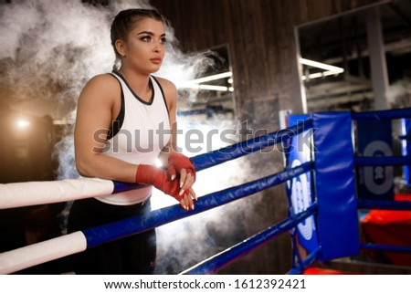 confident caucasian female boxer in sportive wear in ring, love boxing, box is her hobby. Professional boxer woman wearing red protective bandages on hands #1612392421