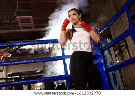 young and beautiful caucasian female in sportive wear training in ring, have fit muscular body, ready to fight in combat readiness. Sport, fitness, boxing concept #1612392970