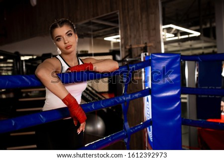 Tired woman boxer after intense training in ring, stand leaning on fence, effective training in gym. #1612392973