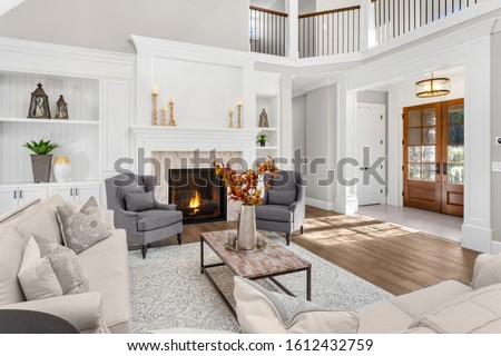 Beautiful living room in new traditional style luxury home. Features vaulted ceilings, fireplace with roaring fire, and elegant furnishings. Shows foyer front door. Royalty-Free Stock Photo #1612432759