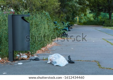Trash next to a trash can in the park, plastic trash next to a trash can #1612434460