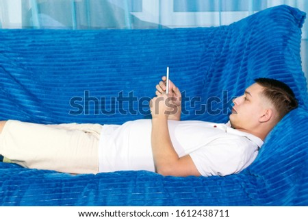 young man in a white t-shirt is lying on the sofa with a phone #1612438711