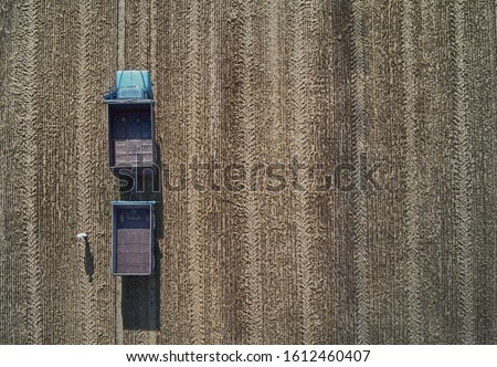Empty harvester truck with trailer in field. Aerial view Royalty-Free Stock Photo #1612460407