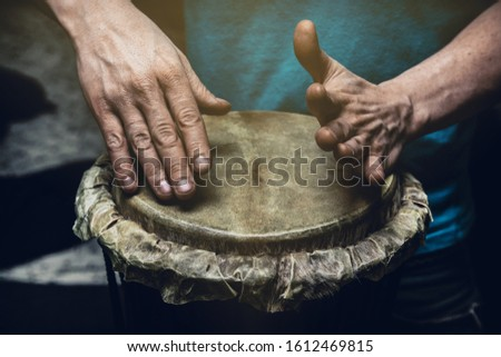 Ethnic percussion musical instrument jembe and male hands #1612469815