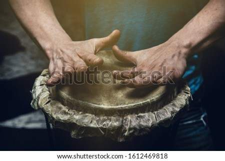 Ethnic percussion musical instrument jembe and male hands #1612469818