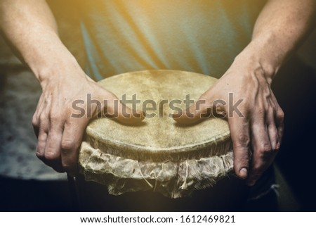 Ethnic percussion musical instrument jembe and male hands #1612469821