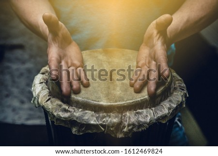 Ethnic percussion musical instrument jembe and male hands #1612469824