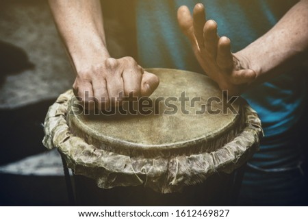 Ethnic percussion musical instrument jembe and male hands #1612469827