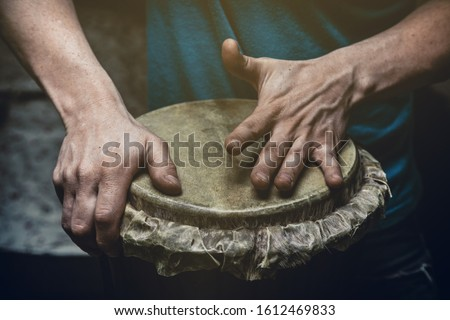 Ethnic percussion musical instrument jembe and male hands #1612469833