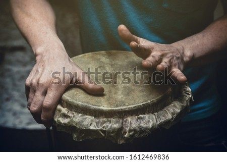 Ethnic percussion musical instrument jembe and male hands #1612469836