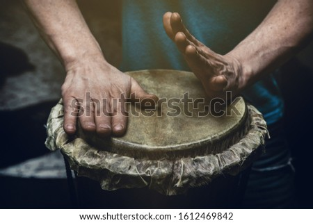 Ethnic percussion musical instrument jembe and male hands #1612469842