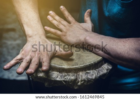 Ethnic percussion musical instrument jembe and male hands #1612469845