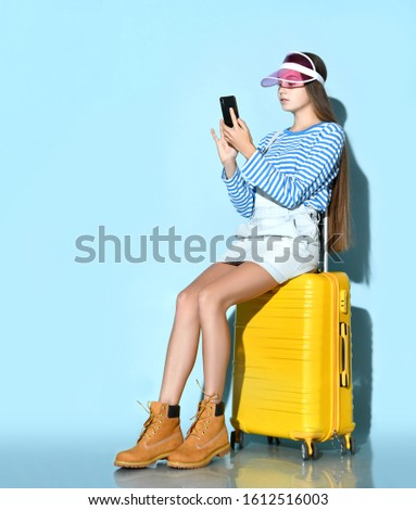 Teenage female in jeans overall skirt, striped sweatshirt, boots, pink sun visor cap. She using smartphone, sitting on yellow suitcase, blue background. Hipster style, fashion. Copy space. Full length #1612516003