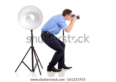 successful young photographer taking photos in studio