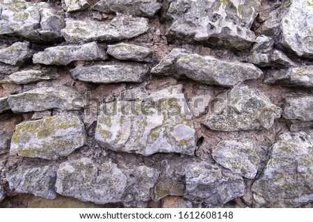 Historic stones. Rough natural masonry with wide seams on a medieval watchtower. Light rough stone. #1612608148