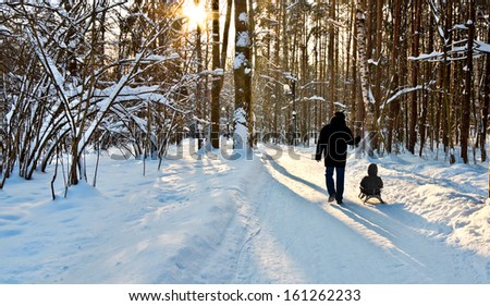 A man with a child in a winter park. Winter landscape.  #161262233