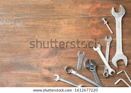 Auto mechanic's tools on wooden background, flat lay. Space for text #1612677220