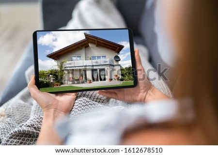 Young Woman Selecting New House On Digital Tablet #1612678510