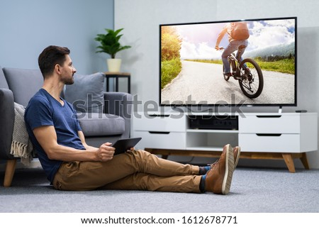 Man Streaming Television Channel Through Wireless Connection On Digital Tablet #1612678771