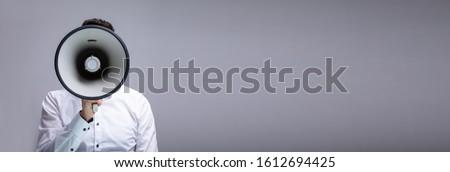 Man Making Announcement Using Megaphone Against Gray Background Royalty-Free Stock Photo #1612694425