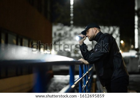 Security Guard Walking Building Perimeter With Flashlight At Night Royalty-Free Stock Photo #1612695859