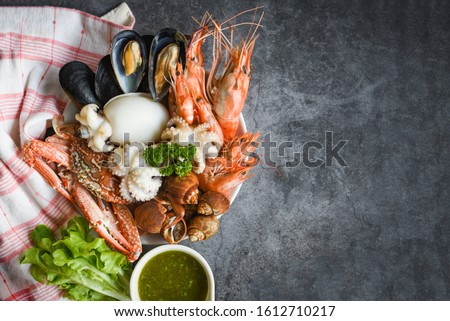 Fresh shrimps prawns squid mussels  spotted babylon shellfish crab and seafood sauce lemon on plate black stone background top view copy space / Cooked steamer food served seafood buffet concept  #1612710217