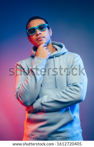 Serious calm peaceful and confident young latin hispanic man on picture. Posing alone with holding fingures on chin. Look straight through sunglasses.