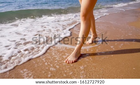 A woman walks along the golden sand of a beach. Female legs walk by the sea. Bare feet of a woman walking along a sandy shore with waves. Summer vacation or vacation. #1612727920
