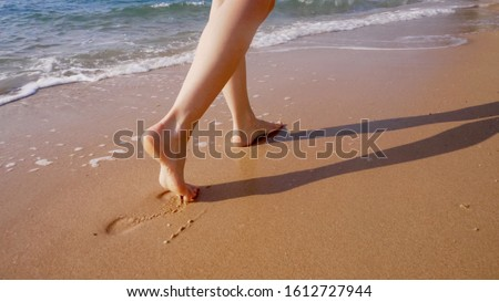 A woman walks along the golden sand of a beach. Female legs walk by the sea. Bare feet of a woman walking along a sandy shore with waves. Summer vacation or vacation. #1612727944