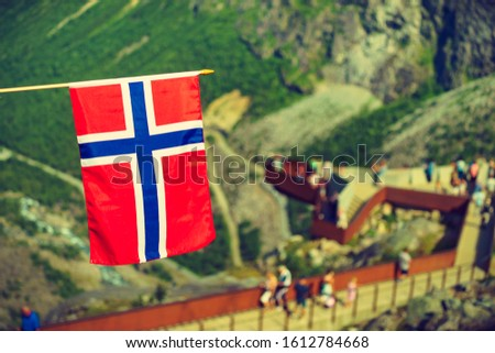 Trollstigen mountain road landscape in Norway, Europe. Norwegian flag waving and many tourists people on viewing platform in background. National tourist route. #1612784668