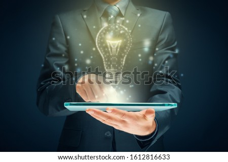 Creative company give you their creativity and ideas. Hands with digital tablet and graphics light bulb - symbols of idea, creative thinking, innovations and intelligence. #1612816633