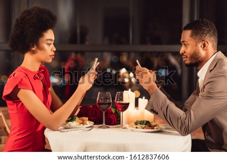 Modern Relationship. Serious African American Couple Using Mobile Phones Having Romantic Date In Restaurant. #1612837606