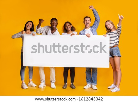 Happy smiling group of multiracial students standing together and displaying white blank placard, yellow studio background